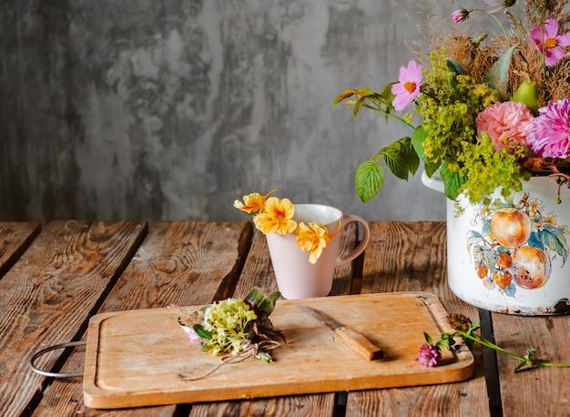 Een oude pot met een compositie van bloemen op een houten rustieke tafel tegen een betonnen muur.