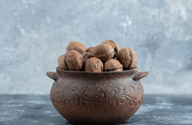Een oude pot vol gezonde walnoten op een grijze muur.