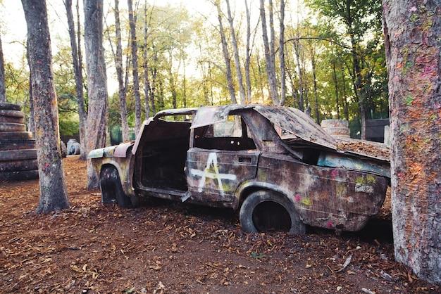 Een oude roestige en verlaten auto bij een paintballbasis
