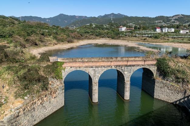 Een oude stenen brug is over de rivier