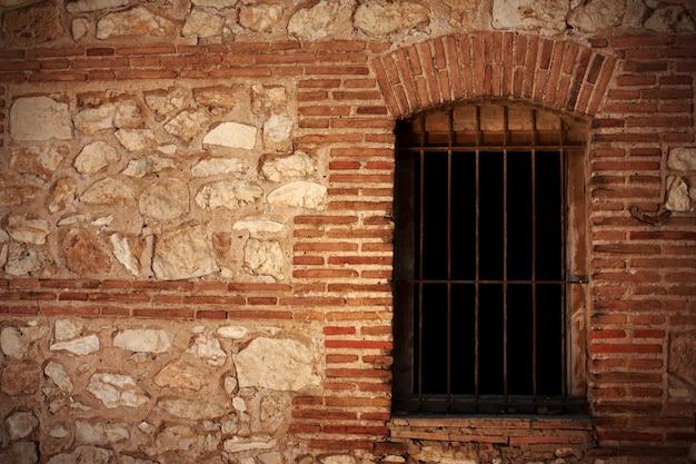 Een oude stenen muur en een raam met tralies
