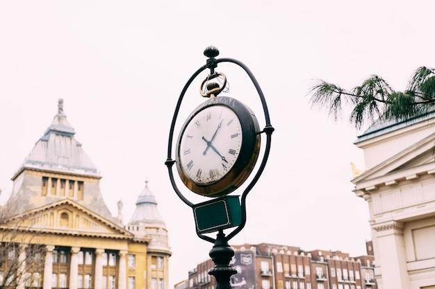 Een oude straatpost met een klok in de straten van boedapest