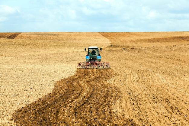 Een oude tractor ploegt de grond in een veld terwijl hij het veld voor het zaaien voorbereidt
