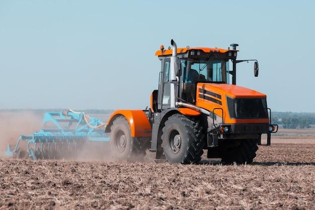 Een oude tractor werkt in het veld. landbouw werk.