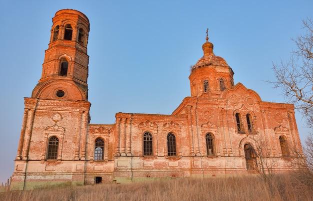 Een oude verlaten en verwoeste kerk, afbrokkelende tempel van rode baksteen