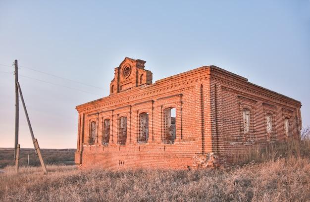 Een oude verlaten en verwoeste kerk die door zonsondergangzon wordt verlicht.