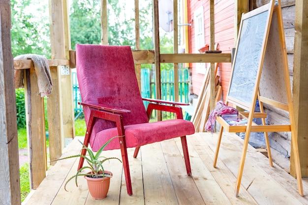 Een oude vintage fauteuil op een open veranda op een plankenvloer, naast een ezel en een aloë bloempot.