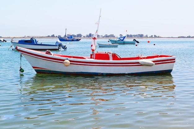 Een oude vissersboot en schepen in de haven.