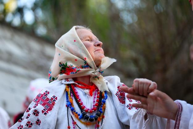 Een oude vrouw danst een dans in nationale kleding. etnische slavische dansen. grootmoeder danst