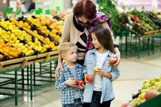 Een oude vrouw, een oma met kleinkinderen kiezen groenten en fruit in een grote supermarkt.