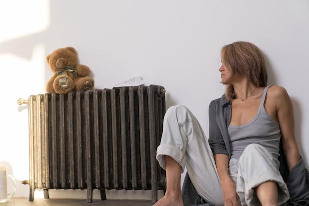 Een oude vrouw in haar appartement zit op de grond en kijkt naar een teddybeer die op een batterij zit