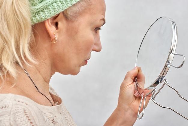 Een oude vrouw kijkt in de spiegel voordat ze make-up aanbrengt