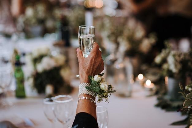 Een oude vrouw met een glas champagne met een bloem vastgemaakt op een accessoire op haar hand