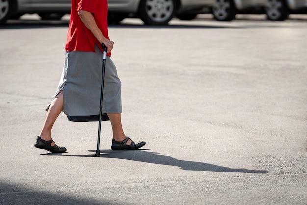 Een oude vrouw met een stok steekt de straat over.