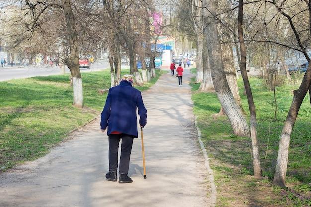 Een oude vrouw met stok loopt over straat. oma heeft hulp nodig