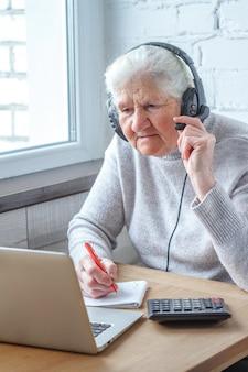 Een oude vrouw zit aan een tafel voor een laptop met koptelefoon en schrijft in een notitieblok.