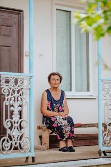 Een oude vrouw zit op een veranda met een smeedijzeren hekwerk