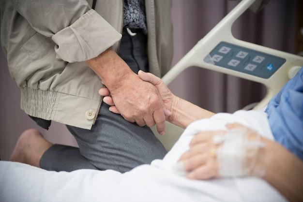 Een oude vrouwen zieke patiënt die op bed ligt dat haar echtgenoothand in het ziekenhuis houdt
