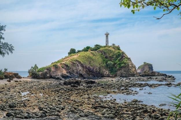 Een oude vuurtoren bovenop een klif dichtbij een rotsachtige kust