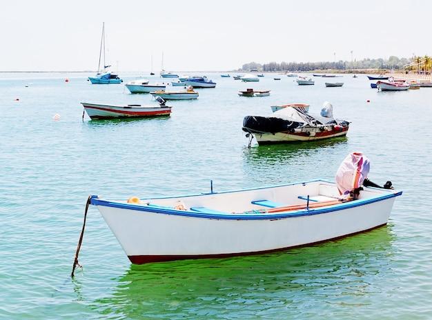 Een oude witte vissersboot en schepen in de haven.