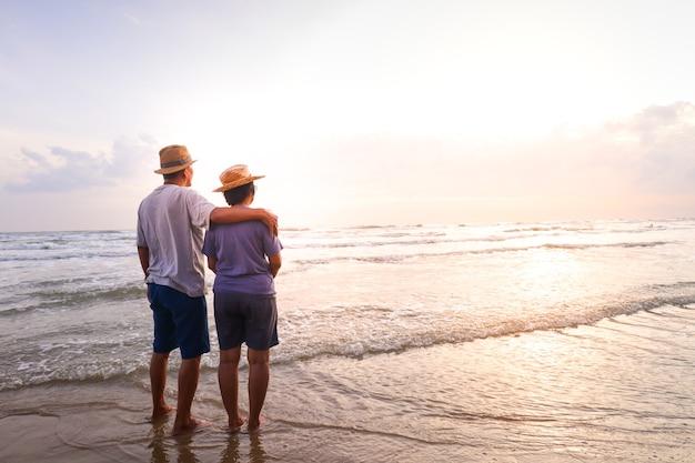 Een ouder aziatisch echtpaar staan samen op het strand kijk samen naar de prachtige zee in de ochtend. reisconcept om gelukkig te leven in de pensioengerechtigde leeftijd. kopieer ruimte