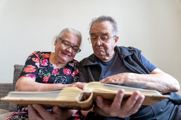 Een ouder echtpaar bekijkt foto's in een familiefotoalbum.
