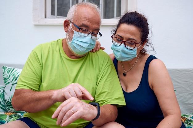 Een ouder echtpaar dat gezichtsmaskers draagt en een videogesprek voert met behulp van een tablet