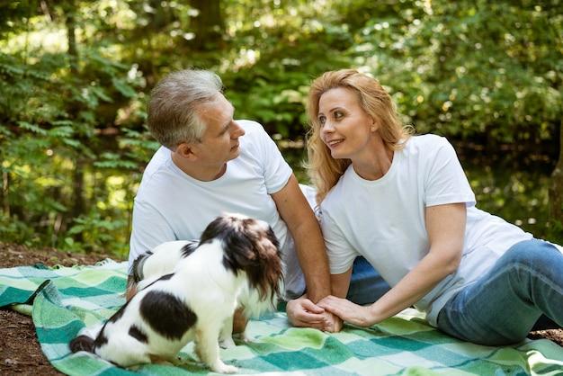 Een ouder echtpaar is aan het relaxen op een picknick in het bos en speelt met een hond op een deken