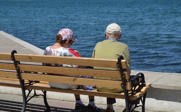 Een ouder echtpaar kijkt naar de zee, zittend op een bankje. het concept van recreatie