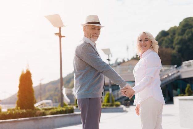 Een ouder echtpaar loopt hand in hand rond.