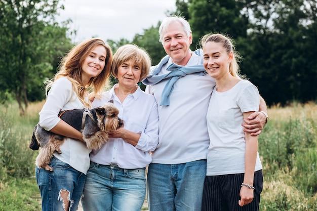 Een ouder echtpaar loopt met volwassen dochters in de natuur. ouder paar wandelen in het bos met een hond. een familie in witte t-shirts en spijkerbroek loopt in het park. familie communiceert buitenshuis
