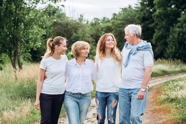 Een ouder echtpaar loopt met volwassen dochters in de natuur. ouder paar wandelingen in het bos. een familie in witte t-shirts en spijkerbroek loopt in het park. gelukkig gezin. familie communiceert buitenshuis