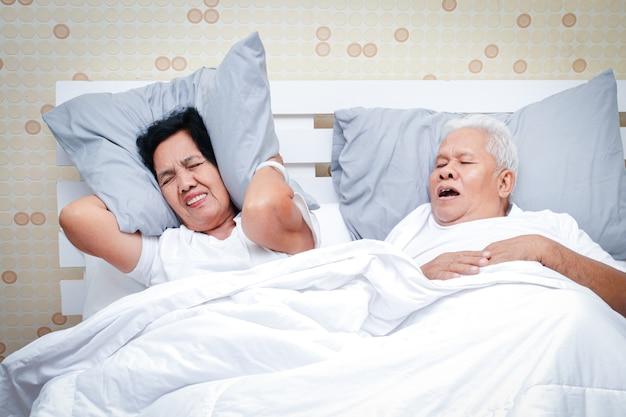 Een ouder echtpaar slaapt in een bed