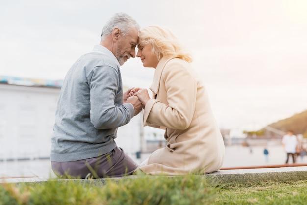 Een ouder echtpaar zit op de rand van een bloembed.