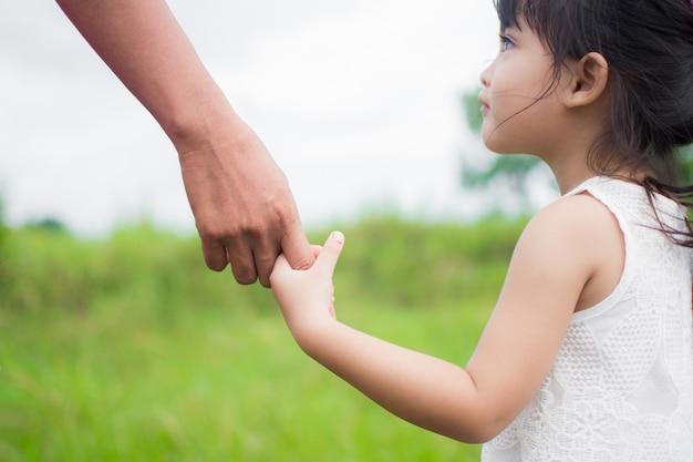 Een ouder heeft de hand van een klein kind, buiten de natuur