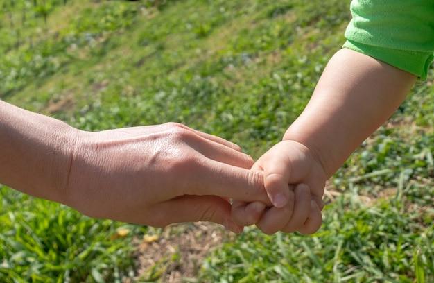 Een ouder houdt de hand van een klein kind vast. het kind houdt de hand van zijn moeder vast. het concept van de kinderdag. kinderdag, moederdag