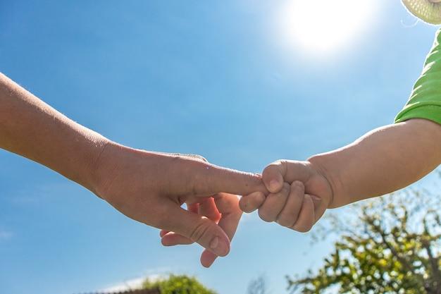 Een ouder houdt de hand van een klein kind vast het kind houdt zijn moeders hand vast kinderdag