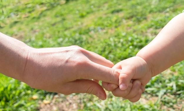 Een ouder houdt de hand van een klein kind vast het kind houdt zijn moeders hand vast op kinderdag