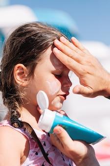 Een ouder smeert zonnebrandcrème op het gezicht van een meisje uit een blauwe tube bij het zwembad van een familiehotel