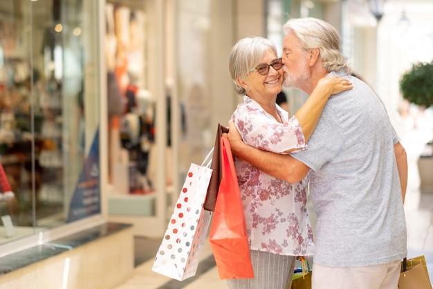 Een ouder stel dat geniet van winkelen in het winkelcentrum geluk en ontspannen met veel tassen