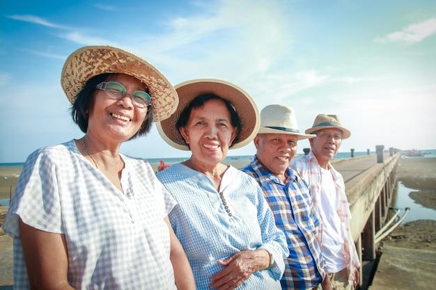 Een oudere aziatische groep staat glimlachend naar de betonnen brug bij de zee, gelukkig na zijn pensionering.