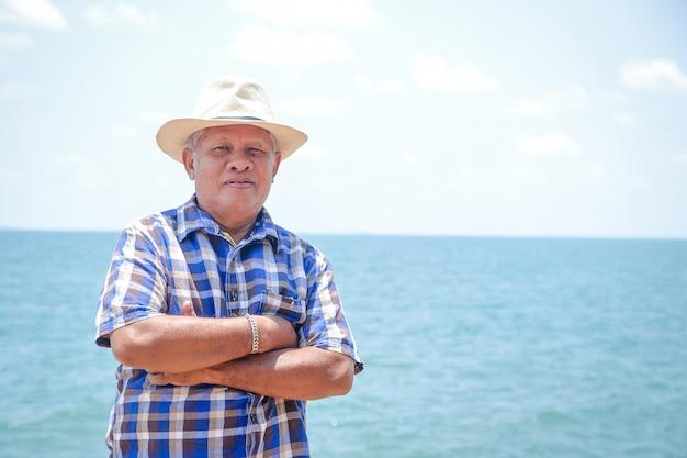 Een oudere aziatische man die een hoed draagt om de zee te bezoeken om te ontspannen