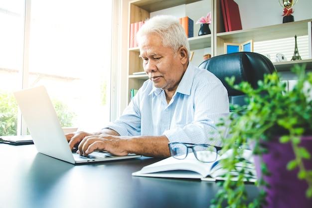 Een oudere aziatische man zat aan het werk en typte een notebookcomputer op kantoor. concept van senior werkgelegenheid, sociale zekerheid, pensionering