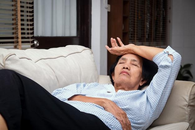 Een oudere aziatische vrouw ligt thuis gestrest op de bank