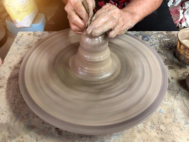 Een oudere aziatische vrouw maakt met de hand aardewerk