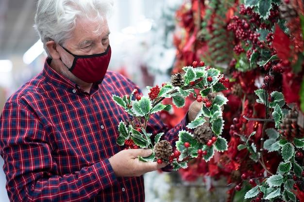 Een oudere, bebaarde man met wit haar die een kerstslinger kiest in een winkel voor de volgende vakantie, draagt een rood masker vanwege het coronavirus