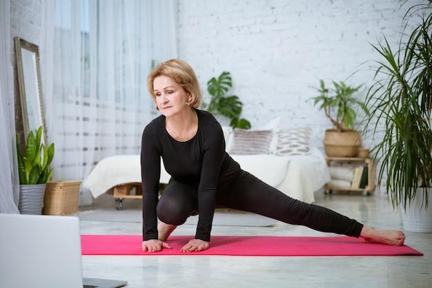 Een oudere blonde vrouw in een zwart trainingspak voert thuis een oefening uit op een sportmat