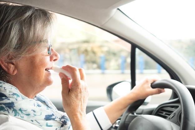 Een oudere dame met grijs haar en een bril die een auto bestuurt. interieur. zijaanzicht. lipgloss in de hand.