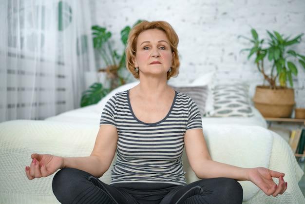 Een oudere kalme vrouw mediteert thuis in de lotushouding