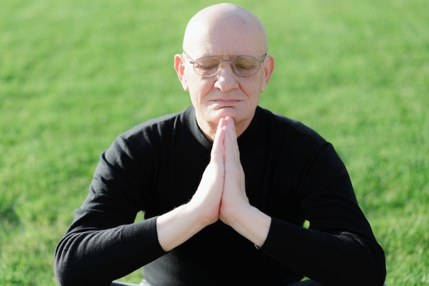 Een oudere man bidt op het gras in wanhoop gebed